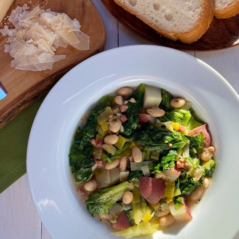 A bowl of beans and greens with Italian bread and Parmesan Cheese