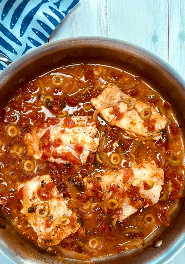 A saute pan with 4 cod fillets in a tomato veracruz sauce