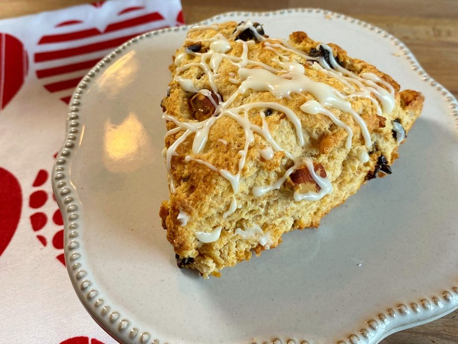 A plate with a dried cherry and almond scone