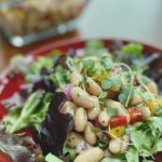 A plate of lettuce topped with an Italian Bean Salad