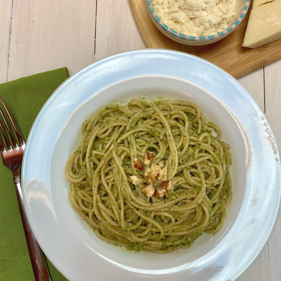A white bowl filled with pasta tossed in a pesto sauce