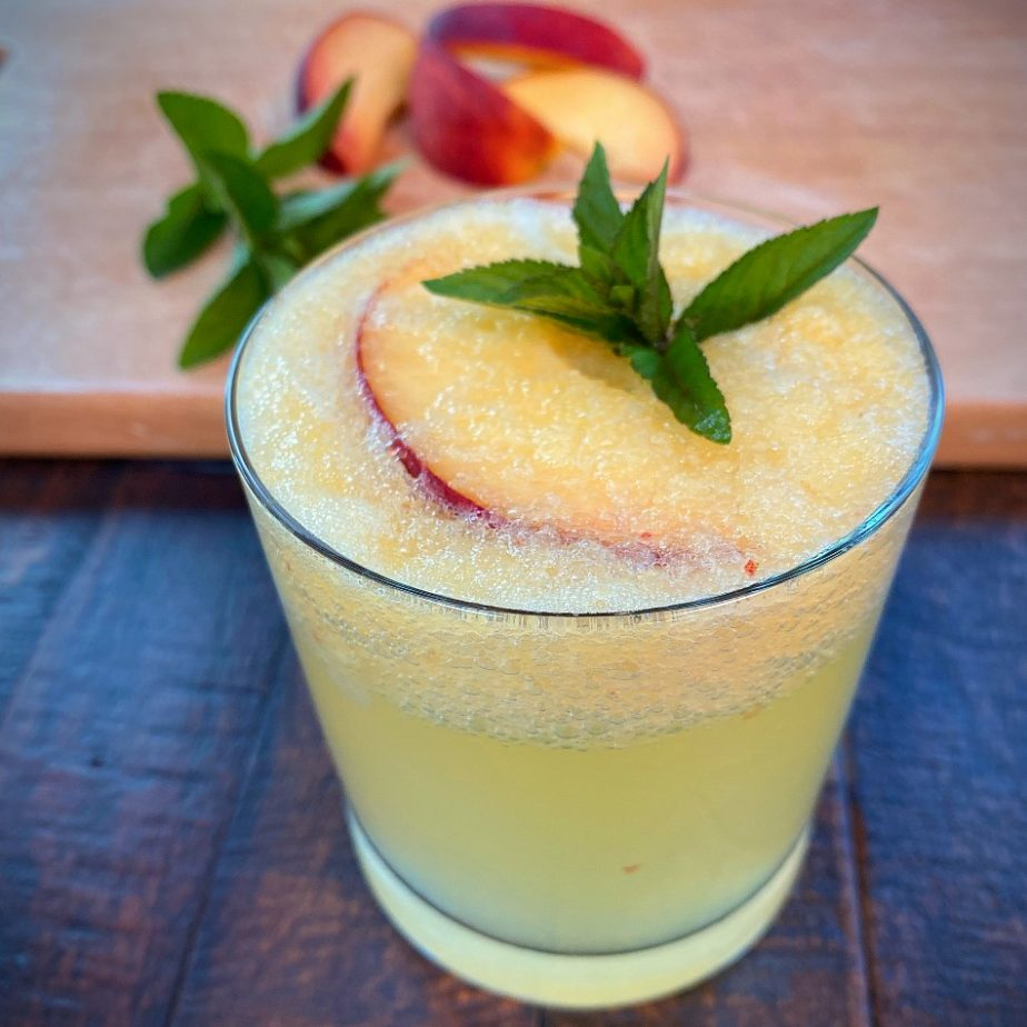 A glass of ginger and peach puree with sparkling water