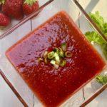A glass bowl of strawberry gazpacho soup