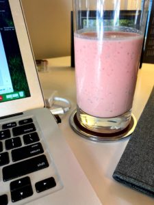 A glass of strawberry watermelon smoothie on desk with a computer