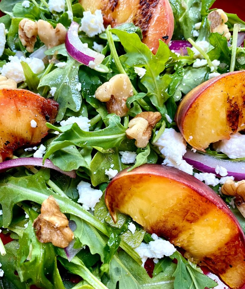 Arugula salad topped with grilled peaches